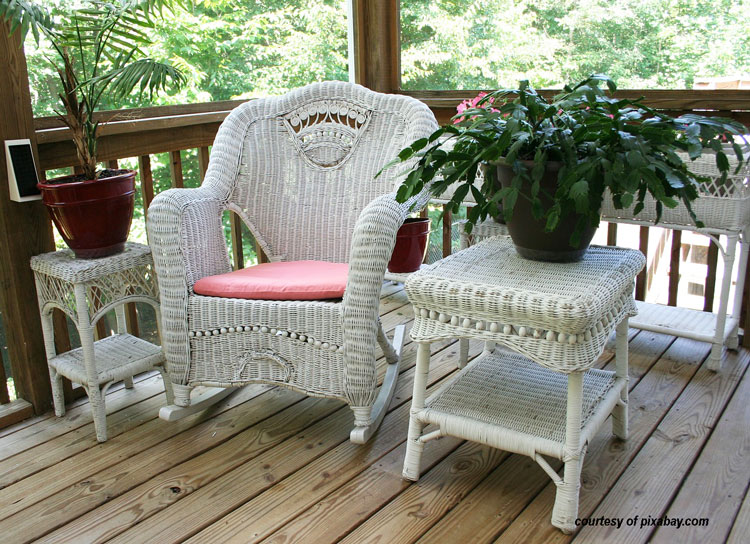 white wicker rocking chair, table, and stand on front porch