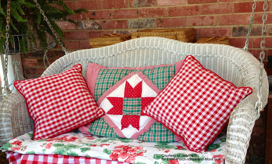 white wicker porch swing with red checked pillows and colorful porch swing cushion