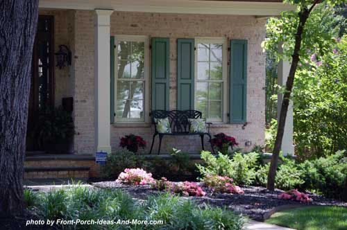lovely green shutters and exquisite landscaping for front porch
