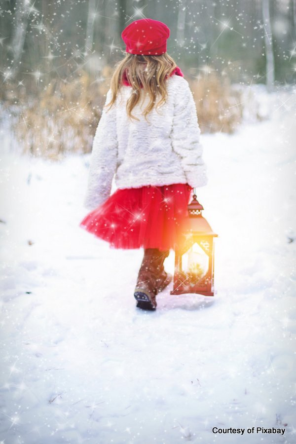 young girl walking in snow with lantern