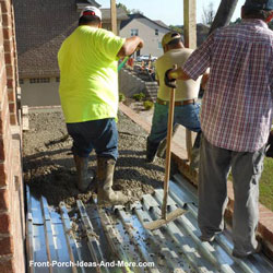 men working concrete for flooring on elevated front porch