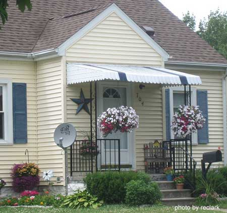 Small yellow home with aluminum porch awnings