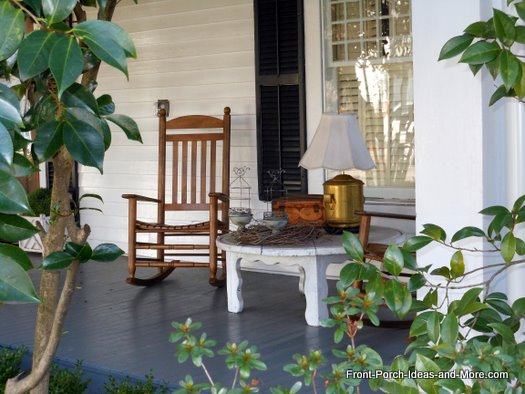 front porch with rocking chair, table, and outdoor lamp