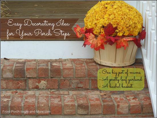 bushel basket with mums and leaf garland on porch steps