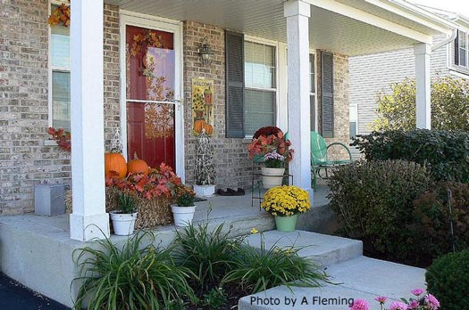 typical decorated fall porch with leaves on straw bale
