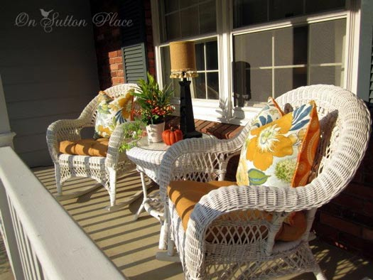 White wicker furniture with colorful autumn pillows