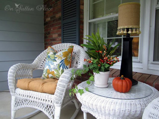 wicker furniture, outdoor lamp, and wicker table on front porch