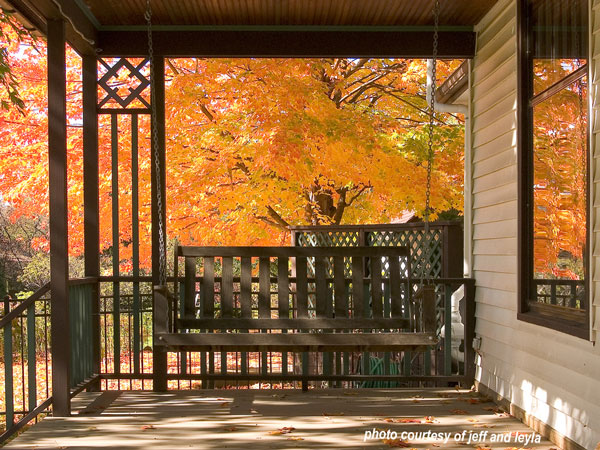 wood swing on front porch in autumn