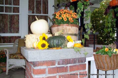 basket filled with mums and pumpkins on front porch