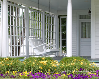 white porch swing on landscaped front porch