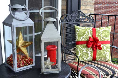 Lanterns and colorful Christmas cushions on porch furniture