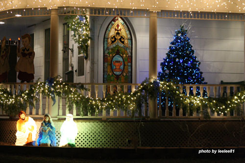 Christmas light idea example - garland, blue christmas tree and nativity scene