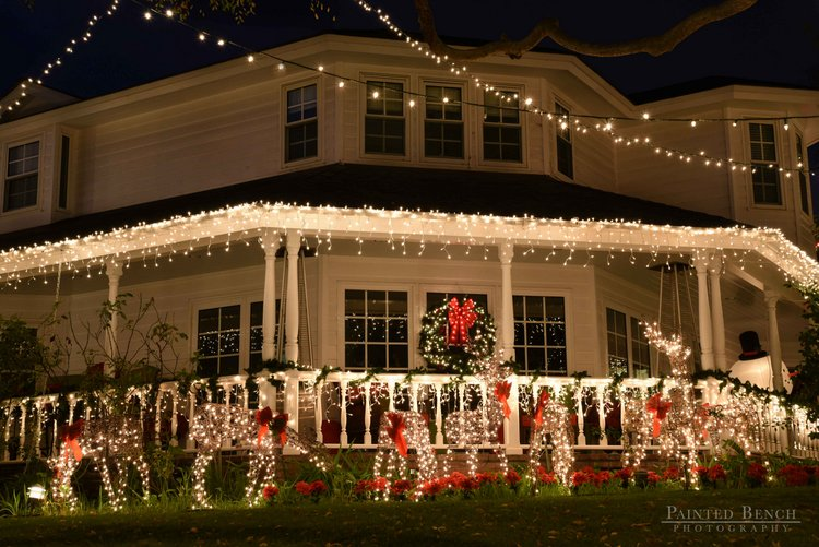front porch beautifully lit with vibrant Christmas lights