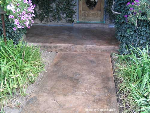 stained concrete porch floor surrounded by flowering plants