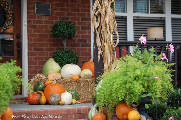 front door and porch decorated for Thanksgiving with pumpkins and corn stalks