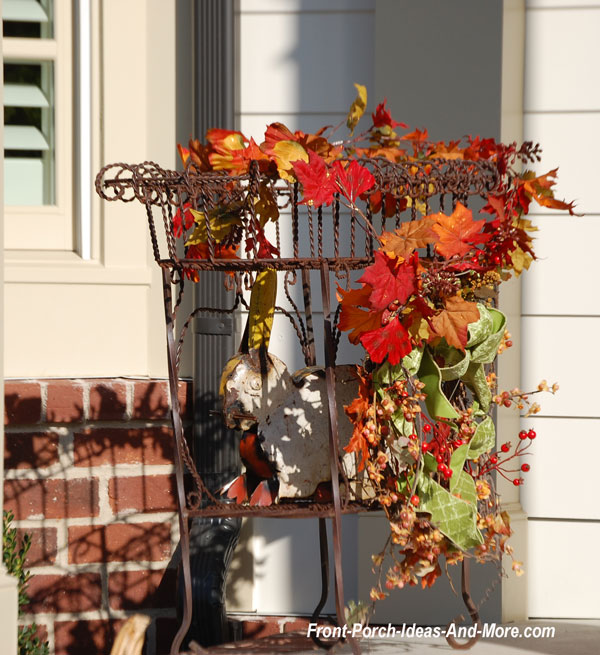 garland laying over metal plant stand on front porch