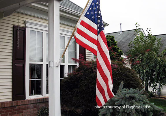 banner flag bracket by FlagBracketPA installed on front porch railing