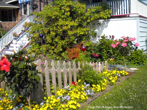 Lovely landscaping along picket fence and around porch