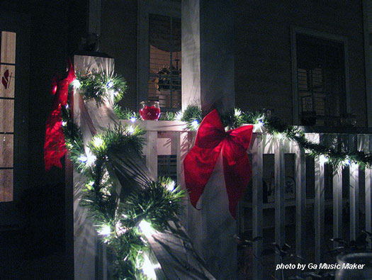 lights and garland wrapped over porch railings