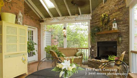 furnished screened porch with plants and fireplace