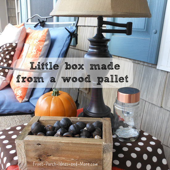Little wooden box filled with hickory nuts on table on front porch