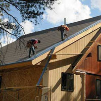 workers installing metal roof on home
