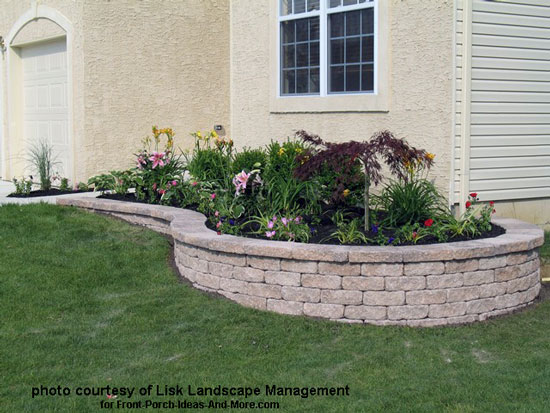 typical planting area transformed with stone retaining wall and colorful plants