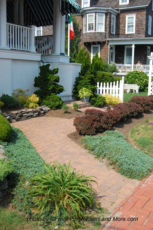nicely landscaped walkway leading to front porch