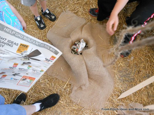 packing newspaper into bucket for scarecrows head