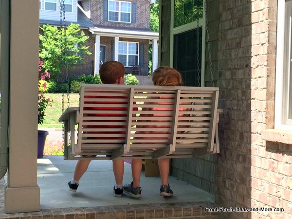 Two of our grandchildren sitting on porch swing