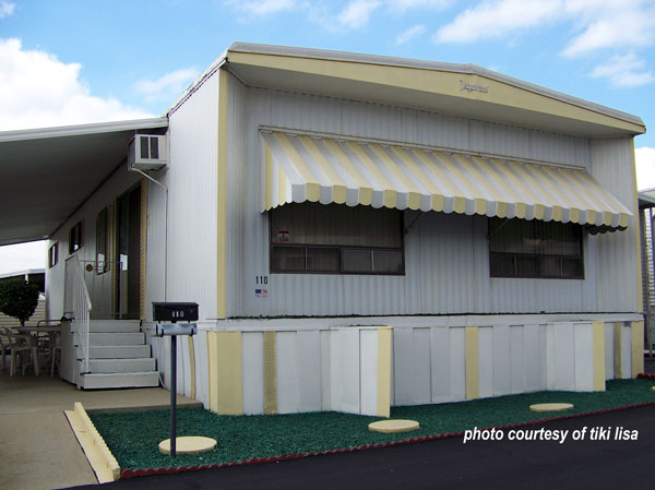 yellow and white stiped awning over windows on mobile home