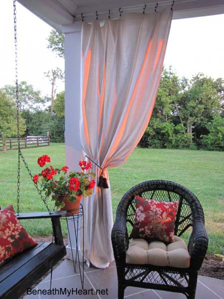 Handmade outdoor curtain panels pulled back on porch corner with a tieback