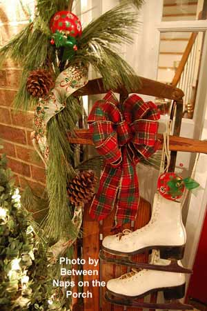 old-fashioned sled with bow wreath, skates and greens on front porch