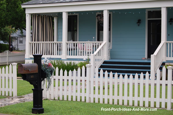 white picket fence with bistro table on front porch
