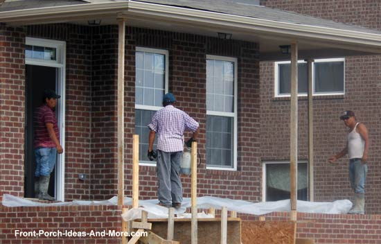 workers laying plastic over newly poured concrete on front porch