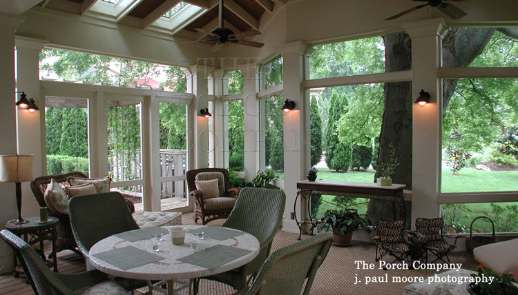 custom screen porch beautifully furnished with ceiling fan, skylights, sconce lights, and more