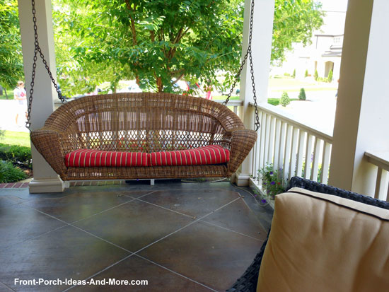 wicker porch swing hanging over tiled porch floor