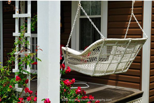 white wicker porch swing on front porch with lattice and climbing roses