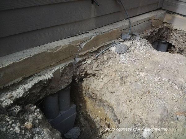 press piles installed under foundation with foundation cracking