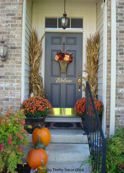 decorated autumn porch with mums and cornstalks