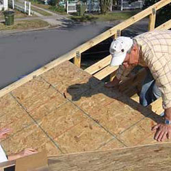 construction worker laying out roofing materials