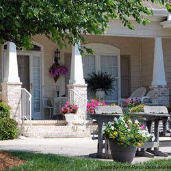 small front porch with craftsman style columns and wicker furniture