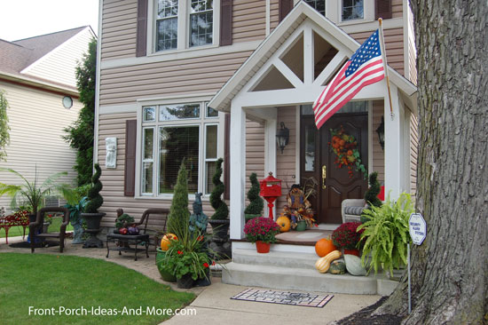 porch extension decorated for autumn with pumpkins and wicker chairs
