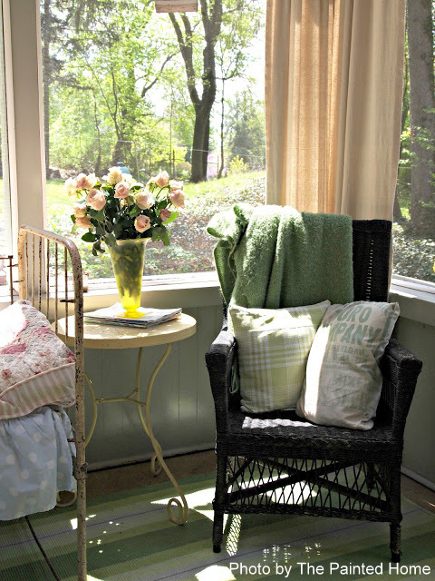 wicker chair in corner of Denise's screened porch. Beautiful scene with vintage style pillows.