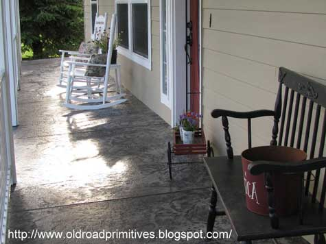 Stamped concrete front porch with rocking chairs and bench