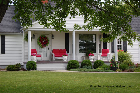 Classic white front porch with red pillows