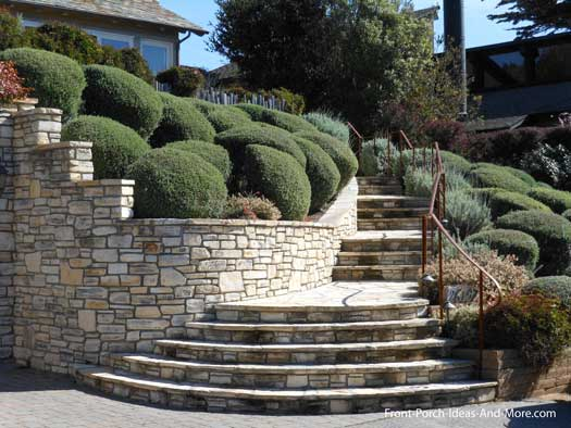 stone steps and evergreen landscaping leading to porch