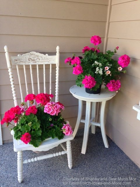 White chair and table with pink geraniums at corner of front porch