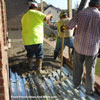men working to level concrete for front porch floor