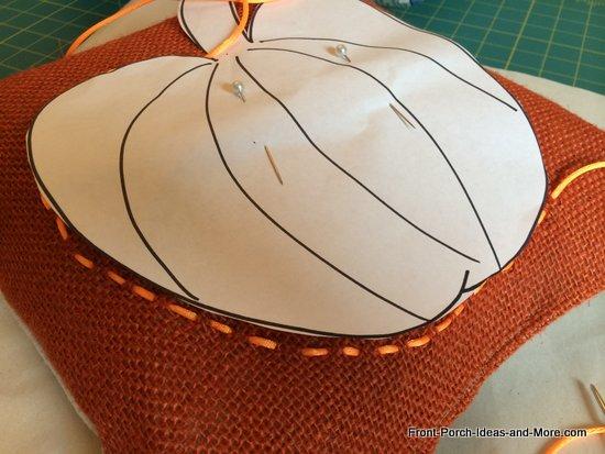 weaving the ribbon into a pumpkin shape onto the burlap